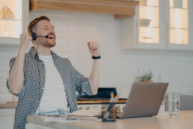 Fröhlicher junger mann mit geschlossenen augen, der triumph feiert, während er zu hause an seinem arbeitsplatz sitzt und ein headset verwendet, männlicher freiberufler, der erfolg genießt, während er zu hause aus der ferne arbeitet gewinnerverhaltenskonzept