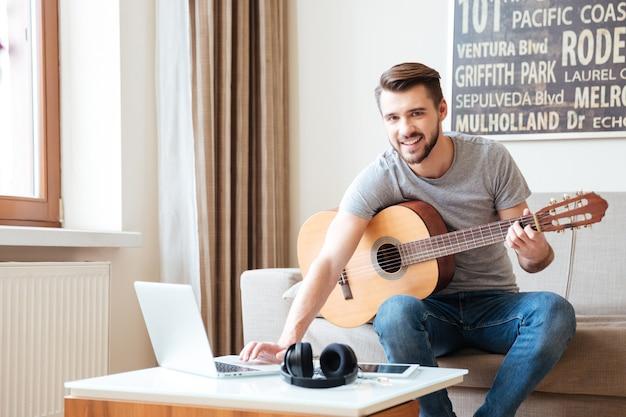 Fröhlicher junger mann mit gitarre, der zu hause musik mit laptop schreibt