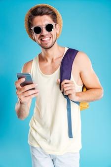 Fröhlicher junger mann mit hut und sonnenbrille mit rucksack mit smartphone