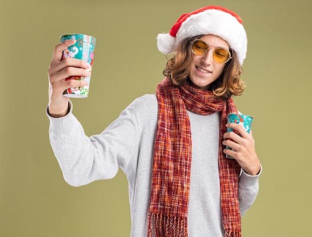 Fröhlicher junger mann mit weihnachtsmütze und gelber brille mit warmem schal um den hals, der bunte pappbecher hält und sie mit einem lächeln im gesicht über grüner wand betrachtet