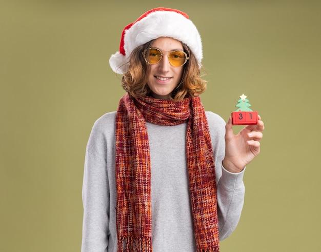 Fröhlicher junger mann mit weihnachtsmütze und gelber brille mit warmem schal um den hals, der spielzeugwürfel mit neujahrsdatum mit lächeln im gesicht über grüner wand hält