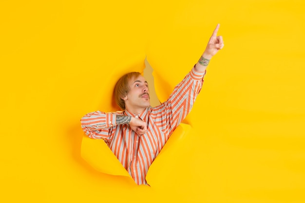 Fröhlicher junger mann posiert in einer zerrissenen gelben papierlochwand emotional und ausdrucksstark
