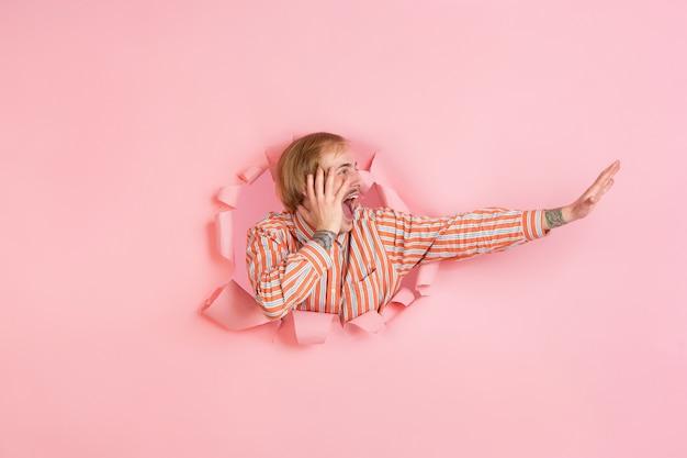 Fröhlicher junger mann posiert in zerrissenem korallenpapierloch, emotional und ausdrucksstark