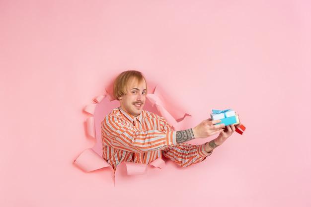 Fröhlicher junger mann posiert in zerrissener korallenpapierlochwand emotional und ausdrucksstark