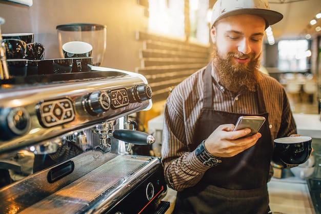 Fröhlicher junger mann steht an kaffeemaschine und schaut auf telefon. er lächelt. guy hält auch eine tasse kaffee. es ist hell im inneren.