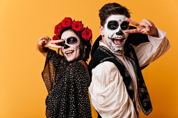 Fröhlicher junger mann und frau haben spaß auf orange wand und zeigen friedenszeichen. porträt eines gemalten paares in nationalen mexikanischen kostümen.