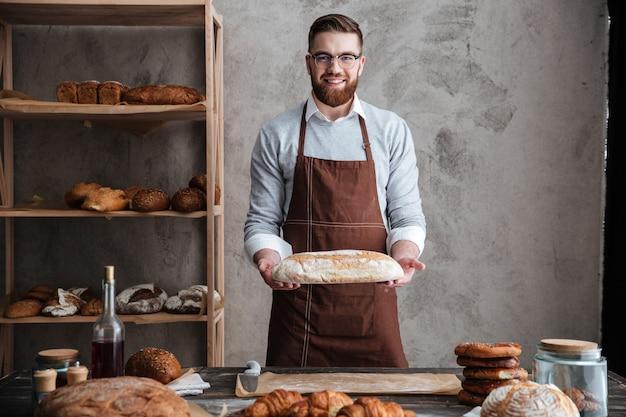Fröhlicher junger mannbäcker, der an der bäckerei steht, die brot hält