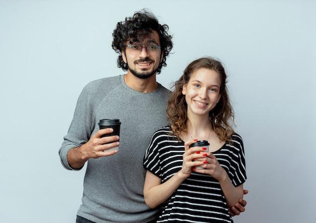 Fröhlicher junger paarmann und frau, die kameras betrachten, die mit glücklichen gesichtern lächeln, während handys stehen, die über weißem hintergrund stehen