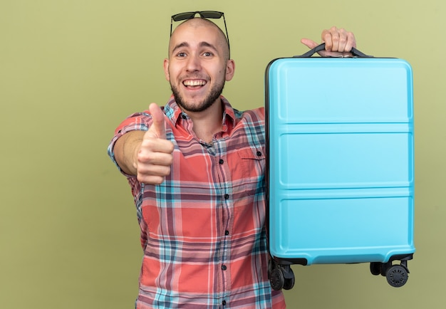 Fröhlicher junger reisender, der koffer hält und isoliert auf olivgrüner wand mit kopienraum nach oben blättert