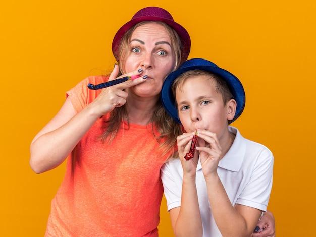 Fröhlicher junger slawischer junge mit blauem partyhut und seiner mutter mit violettem partyhut, die partypfeife isoliert auf oranger wand mit kopierraum bläst