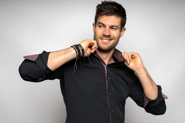 Fröhlicher junger spanischer mann, der ein schwarzes hemd trägt, das gegen eine weiße wand steht