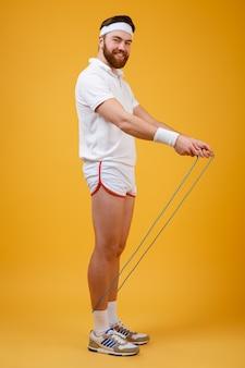 Fröhlicher junger sportler, der springseil hält