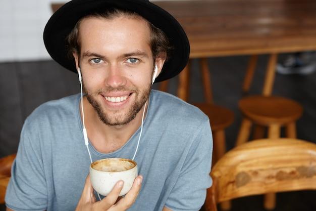 Fröhlicher junger student im lässigen t-shirt und im trendigen hut, der neues kopfalbum seines lieblingskünstlers über kopfhörer hört, mit online-musik-app auf handy