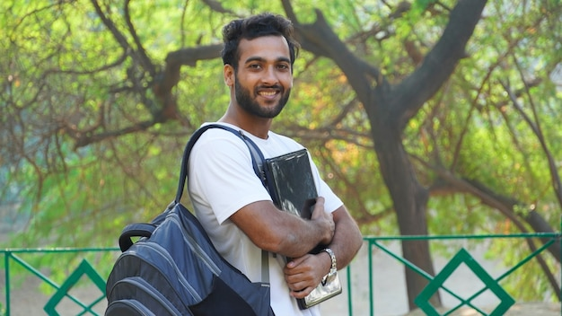 Fröhlicher junger student mit laptop suchen