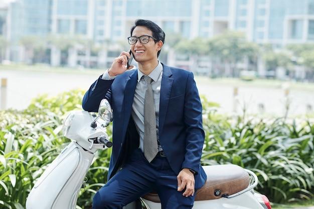 Fröhlicher junger vietnamesischer unternehmer, der auf roller sitzt und am telefon anruft