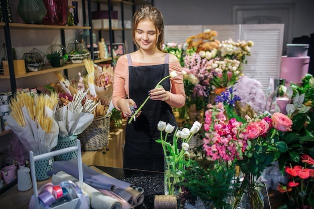 Fröhlicher junger weiblicher florist stehen im blumenladen. sie hält weiße tulpe und schneidet einen teil des stiels. sie lächelt.