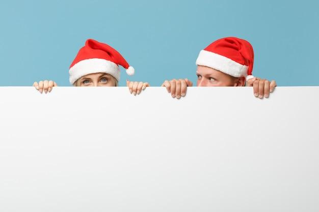 Fröhlicher junger weihnachtsmann-paarfreunde-typ und frau in weihnachtsmütze