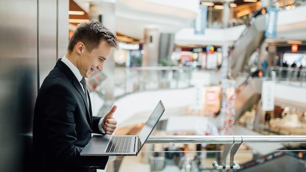 Fröhlicher junger wirtschaftswissenschaftler, der laptop hält und daumen hoch zeigt, glücklich, im schwarzen anzug gekleidet