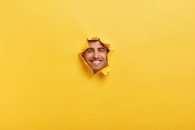 Fröhlicher kaukasischer mann mit zahnigem lächeln, zeigt weiße zähne