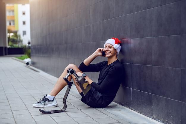 Fröhlicher kaukasischer sportler mit künstlichem bein und mit weihnachtsmütze auf dem kopf, der auf dem boden sitzt, sich an die wand lehnt und am telefon spricht.