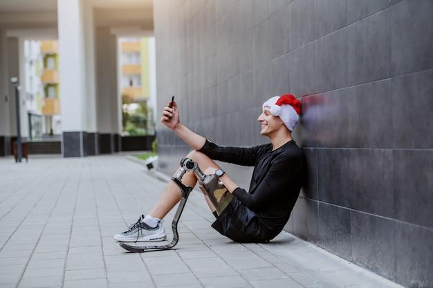 Fröhlicher kaukasischer sportler mit künstlichem bein und mit weihnachtsmütze auf dem kopf, der auf dem boden sitzt, sich an die wand lehnt und selfie macht.