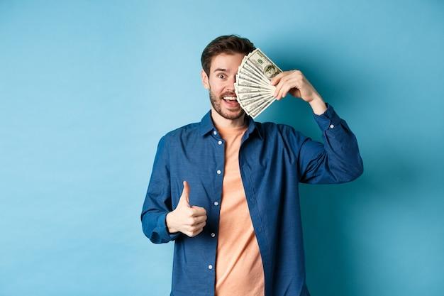 Fröhlicher kerl bedeckt die hälfte des gesichts mit geld und zeigt daumen hoch, empfiehlt einen schnellen geldkredit und steht auf blauem hintergrund.