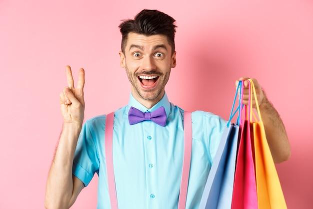 Fröhlicher kerl, der friedenszeichen und einkaufstaschen zeigt, glücklich in der kamera lächelnd, über rosa hintergrund stehend.