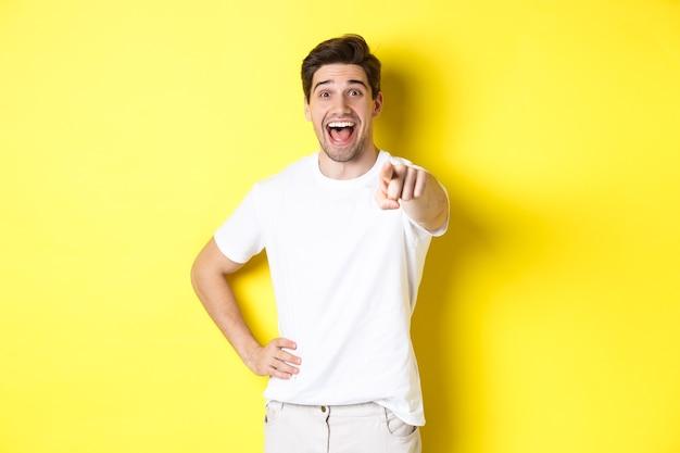 Fröhlicher kerl, der mit dem finger auf die kamera zeigt und lacht, schaut sich etwas an, das auf gelbem hintergrund steht