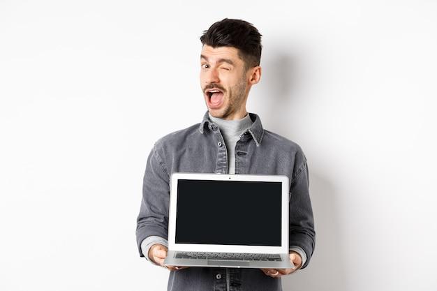 Fröhlicher kerl, der zwinkert und leeren smartphonebildschirm zeigt, bieten ihnen werbung an, die auf weißem hintergrund steht.