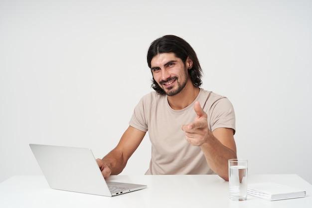 Fröhlicher kerl, glücklicher geschäftsmann mit schwarzen haaren und bart. bürokonzept. am arbeitsplatz sitzen. arbeiten am laptop, isoliert über weißer wand