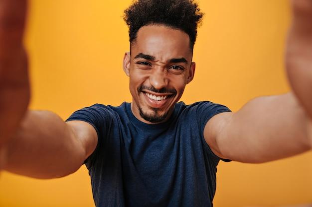 Fröhlicher kerl im blauen t-shirt macht selfie an isolierter wand Premium Fotos