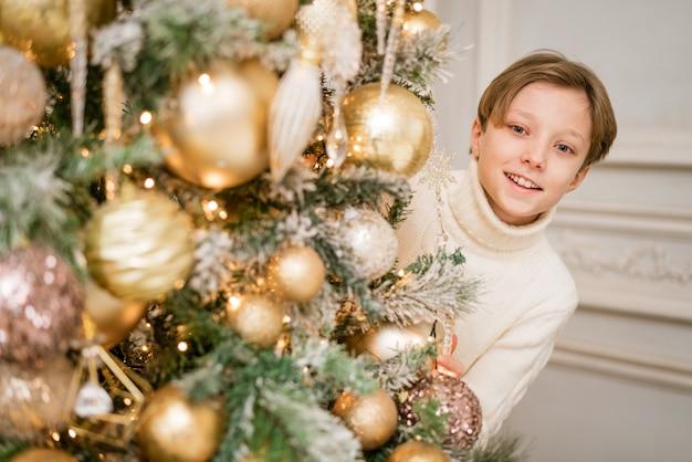 Fröhlicher kerl im pullover am weihnachtsbaum schmückt und schaut von hinten heraus. viel spaß auf c ...