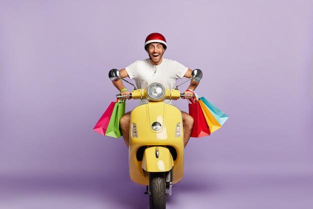 Fröhlicher kerl mit helm und einkaufstaschen, die gelben roller fahren