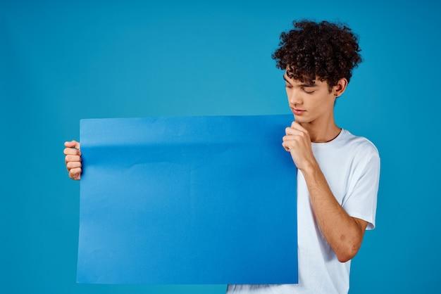 Fröhlicher kerl mit lockigem haar und blauem leerem plakat