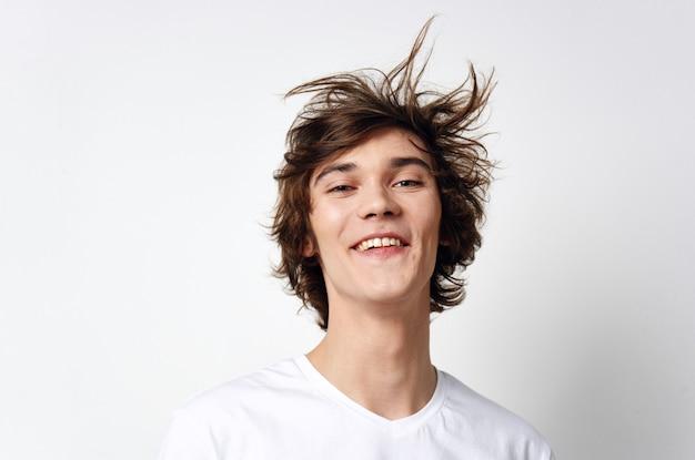 Fröhlicher kerl mit zerzaustem haar in einem weißen t-shirt emotionen nahaufnahme. foto in hoher qualität