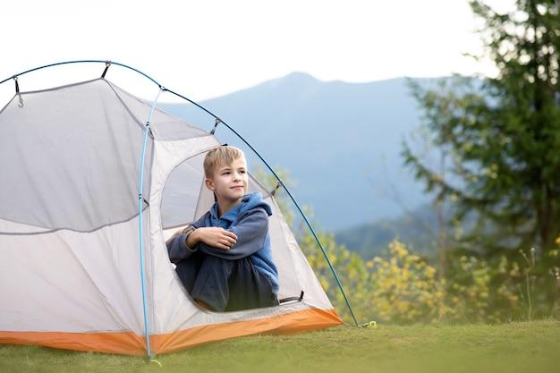 Fröhlicher kinderjunge, der allein in einem touristenzelt auf einem bergcampingplatz ruht und den blick auf die schöne sommernatur genießt. wandern und aktives lebenskonzept.