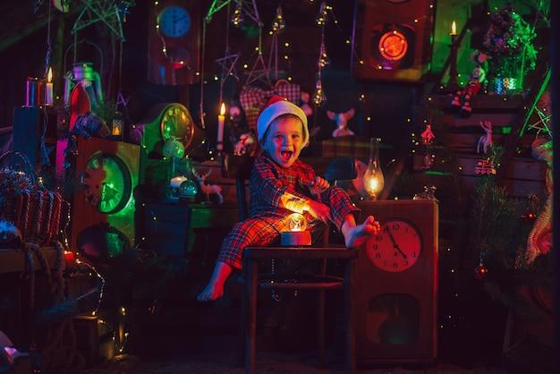 Fröhlicher kinderjunge im weihnachtspyjama und einem hut, der helfer des weihnachtsmanns in der weihnachtszauberdekoration.