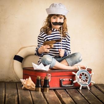 Fröhlicher kinderpirat, der drinnen mit spielzeugsegelboot spielt. reise- und abenteuerkonzept