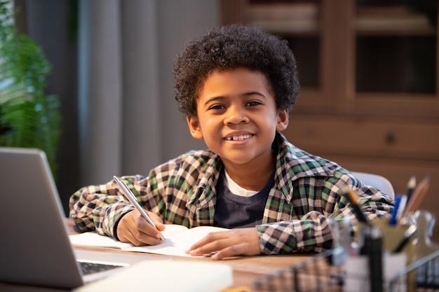 Fröhlicher kleiner afrikanischer schüler, der notizen im schreibheft macht und sie ansieht, während er in der häuslichen umgebung am tisch vor dem laptop sitzt