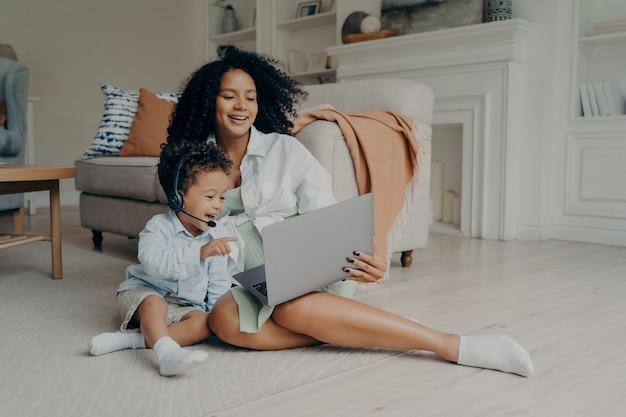 Fröhlicher kleiner junge, der ein headset verwendet, während er online auf einem laptop spricht, der mit mama auf dem boden sitzt?