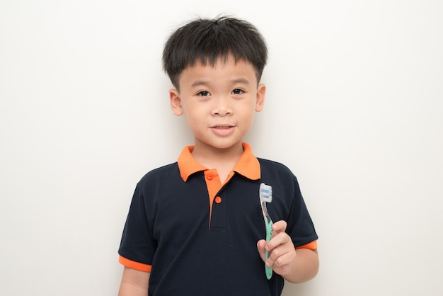 Fröhlicher kleiner junge, der eine zahnbürste auf weißem hintergrund hält, studioporträt eines gesunden mischlingsjungen mit einer isolierten zahnbürste.