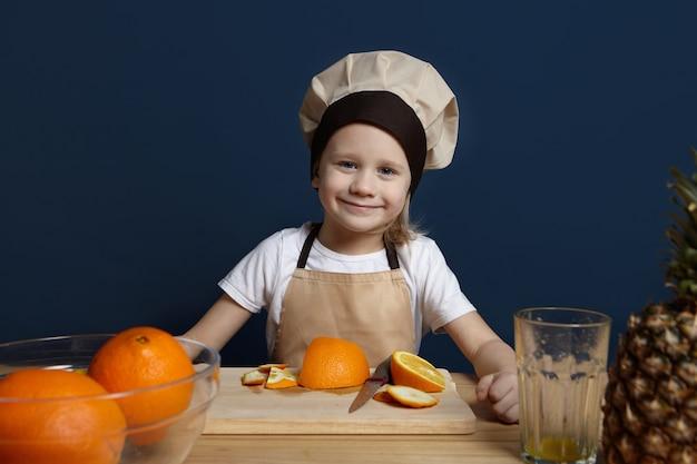 Fröhlicher kleiner junge, der schürze und kochmütze trägt, die in der modernen küche steht und obstsalat kocht. porträt des niedlichen kaukasischen männlichen kindes in der uniform, die frischen saft macht, orangen schneidet und schält