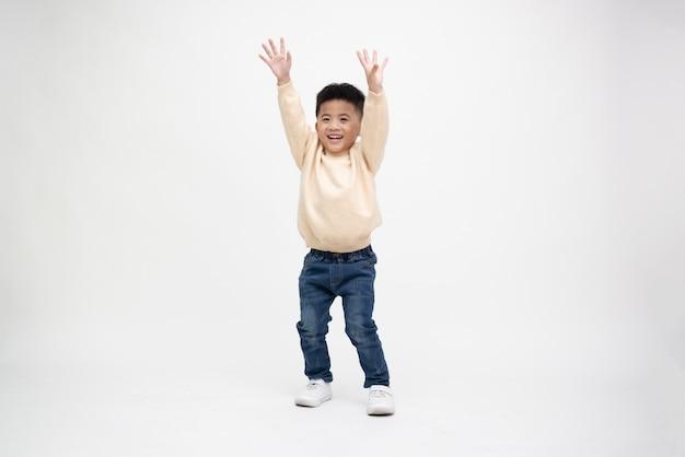 Fröhlicher kleiner junge die hände hoch oder zeigt siegerzeichen isoliert auf weißem hintergrund, glückliches asiatisches kindermodell, personenzusammensetzung in voller länge
