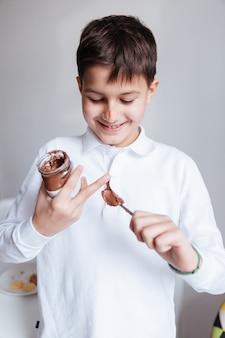 Fröhlicher kleiner junge im weißen hemd isst schokoladenaufstrich aus dem glas mit dem löffel