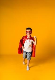 Fröhlicher kleiner junge in einem heldenkostüm auf einer gelben oberfläche mit einem platz für text