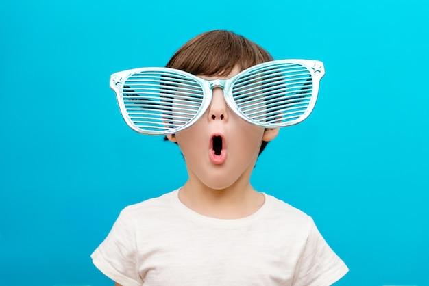 Fröhlicher kleiner junge in großen gläsern drückt ein überraschtes gesicht aus, das auf blauer wand isoliert wird