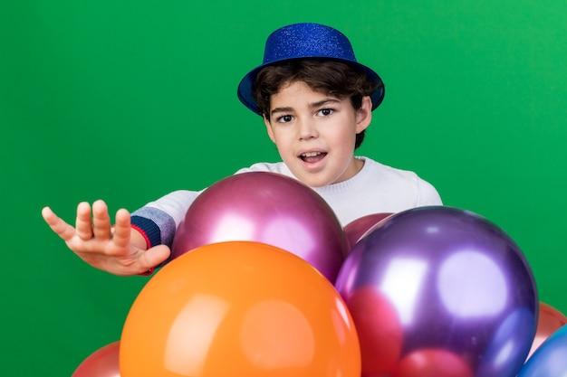 Fröhlicher kleiner junge mit blauem partyhut, der hinter ballons steht und die hand isoliert auf grüner wand hält