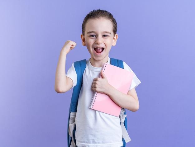 Fröhlicher kleiner junge mit rucksack mit notizblock und ja-geste