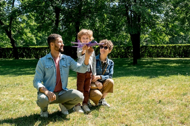 Fröhlicher kleiner junge mit spielzeugflugzeug, das auf grünem rasen zwischen seinen eltern steht, die auf kniebeugen in der nähe sitzen, während sie zeit im park verbringen