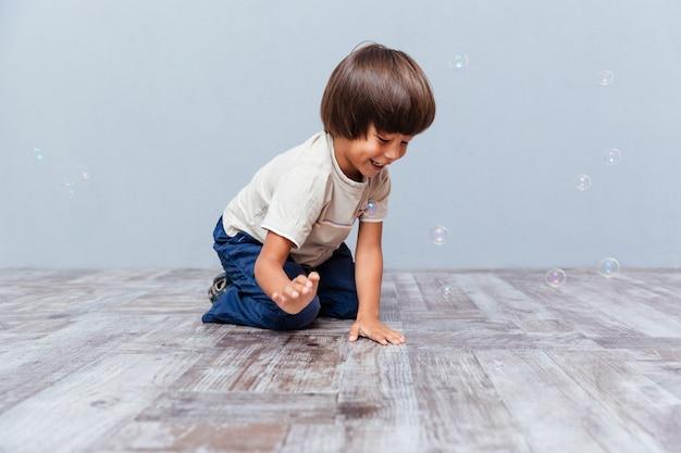 Fröhlicher kleiner junge sitzt und spielt mit seifenblasen